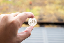 Man Hold Japanese Coin 500 Yen On Blurred Background