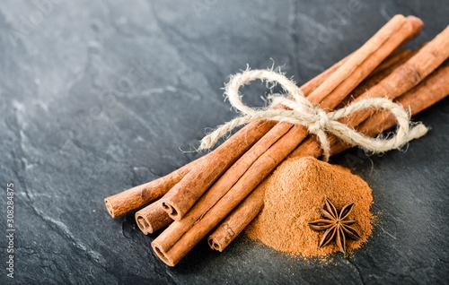 Fototapeta Cinnamons sticks on dark stone table. Dried cinnamon powder with star anise on black board. obraz