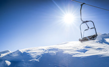 Ski Lift Seats High In The Mountains. Winter Elevator Mountains Panorama With Sun And Blue Sky In Background. Copy Space For Text.