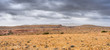 Deserted stony landscape under the dark cloudy sky, multi-shot panorama.