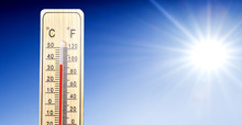 Thermometer In Summer Day Shows Or Indicate High Temperature Degree With Sun In Background..