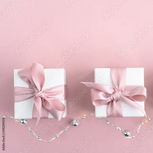 Fototapeta Gift boxes wiyh powdery ribbon. Powdery background. Silver bracelet with charms. Gift box for the New Year and Christmas. Best gift for Valentines Day and Mothers day. obraz na płótnie
