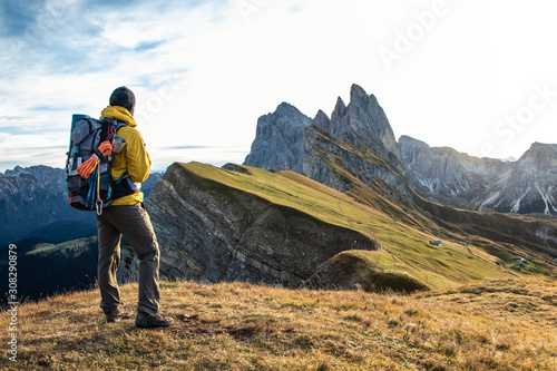 Obraz Young man hiking at Seceda mountain peak at sunrise. Backpack, yellow jacket, boots, beanie. Traveling to puez Odle, Dolomites, Trentino, Italy. - fototapety do salonu