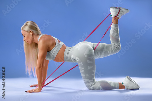 Valokuvatapetti Fitness woman doing exercise for glutes isolated on blue background