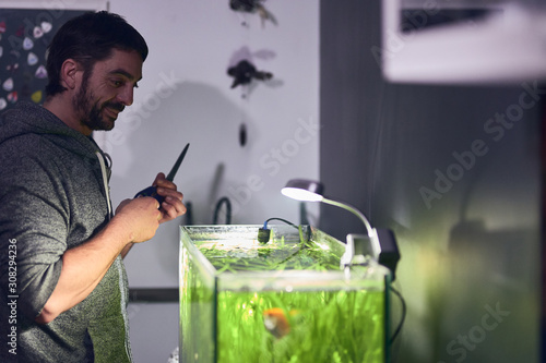 Young smiling boy looking at his aquarium with pruning scissors in his hands Wallpaper Mural