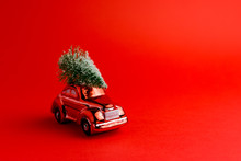 Red Toy Car With A Christmas Tree On The Roof, Red Trend Background. New Year Concept