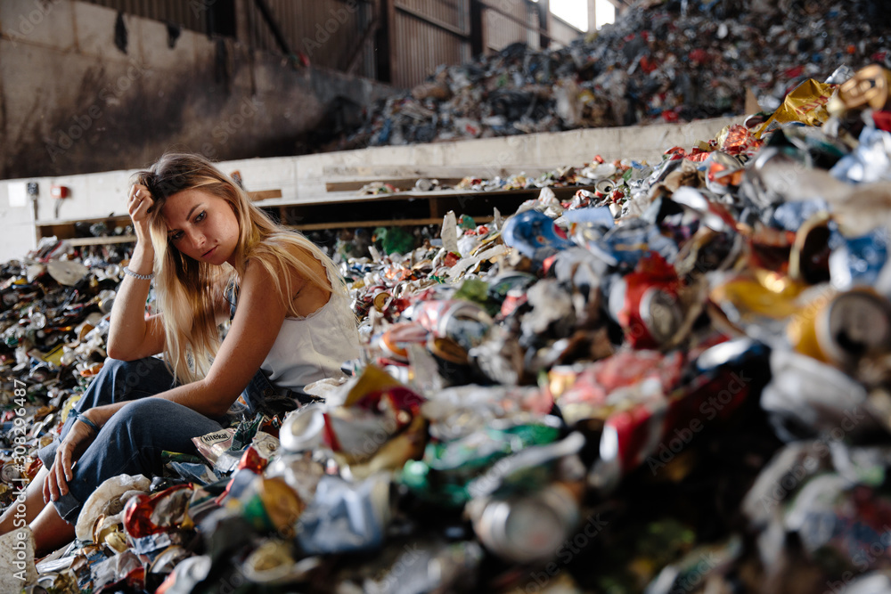Fototapeta Young blonde nature pollution activist sits at huge trash dump. Looks at all human waste and plastic, Eastern Europe Latvia Riga
