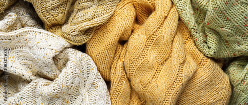 Pile of Knitted Winter Sweaters. Piles of clothes background Wallpaper Mural