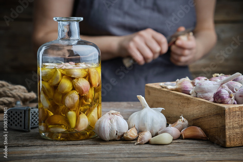Fotografía Garlic aromatic flavored oil or infusion bottle and wooden crate of garlic cloves on wooden kitchen table