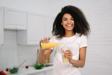 Young Beautiful African American Woman Holding Glass With An Orange Juice, Looking At Camera And Smiling. Healthy Lifestyle Concept, Natural Organic Breakfast At Kitchen