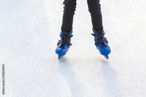 Cuadros en Lienzo  man actively rides in blue skates on an ice rink