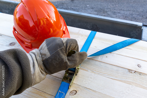 Construction worker secures load on a car trailer with tension straps #308315271