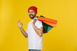 canvas print picture - Photo of happy guy, holding shopping bags, isolated over yellow background