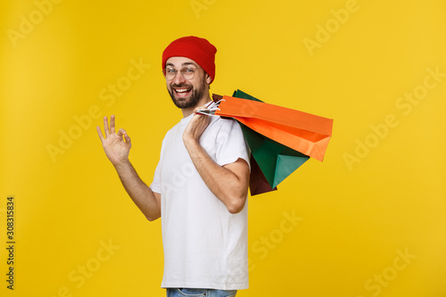 Papel de parede Photo of happy guy, holding shopping bags, isolated over yellow background