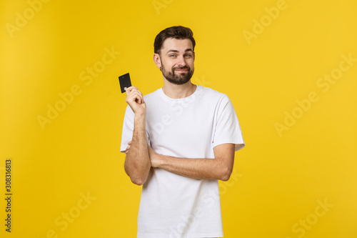 Fotomural  Happy smiling young man showing credit card isolated on yellow background