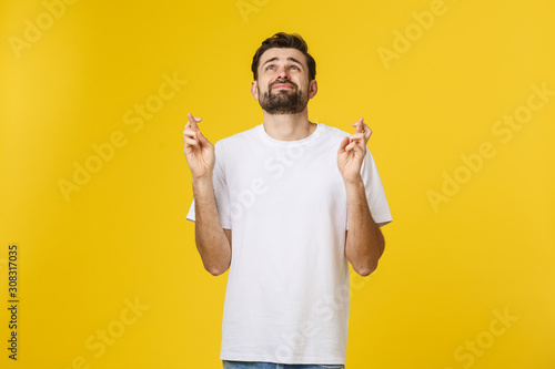 Fotomural Young man making a wish isolated on yellow background