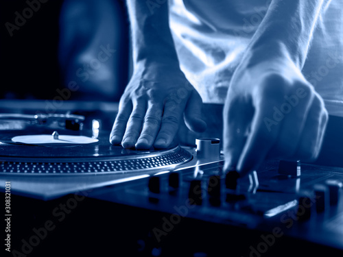 Fotografie, Tablou  dj hands on professional music equipment deck vinyl record turntable and timecod