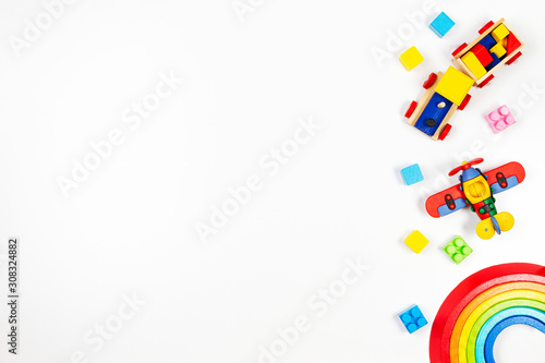 Obraz Baby kids toys background. Wooden train, red plane, stacking rings rainbow toy and colorful blocks. Top view, flat lay - fototapety do salonu