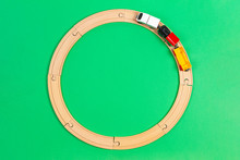Toy Train Moves On Round Wooden Railways On Light Green Background. Top View