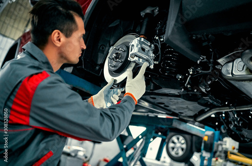 obraz dibond Car mechanic worker repairing suspension of lifted automobile at auto repair garage shop station