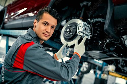 Fotografía Car mechanic worker repairing suspension of lifted automobile at auto repair gar