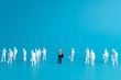 Miniature people concept - a different business worker standout from the crowd