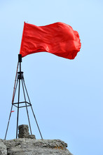 Scarlet Banner Waving In The Wind. A Red Flag At The Top Of High Mountain On Overcast Day. The Vivid Red-colored Flag On The Foreground Of Cloudy Sky