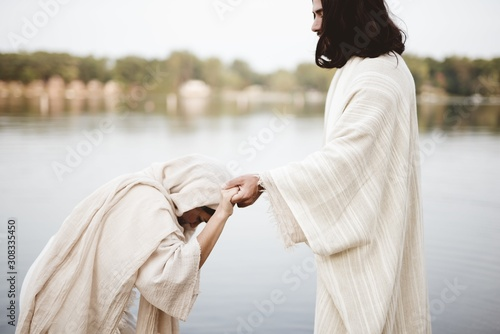 Tablou Canvas Shallow focus shot of a female grabbing the hand of Jesus Christ for healing and