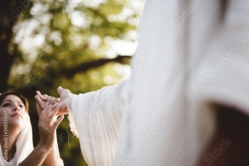 Fotografia Shallow focus shot of a female grabbing the hand of Jesus Christ for healing and
