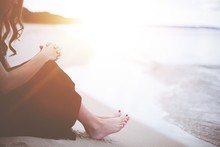 Shallow Focus Shot Of A Female Sitting Near The Beach With Her Hands On Her Knees While Praying