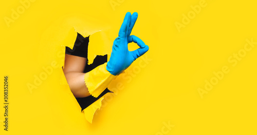 Hand in rubber blue-yellow glove shows OK gesture with fingers Canvas Print