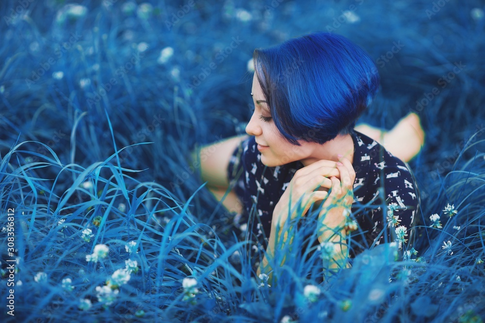 Fototapeta Millennial girl with blue hair. Beautiful young stylish close eyes woman lying down and rest on grass in summer time in the park. Fresh natural summer peace view. Classic blue 2020 year color concept