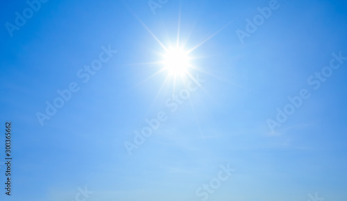 Shining sun with rays and clear blue sky