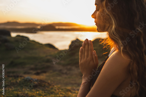 Fotomural Woman praying alone at sunrise