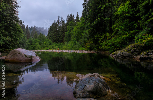 Photo Pine trees reflecting in the crystal clear water of a lake on a cloudy day in Ly