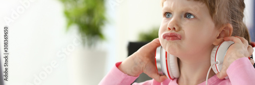 Little girl wearing headphones using computer aggressive articulating Wallpaper Mural