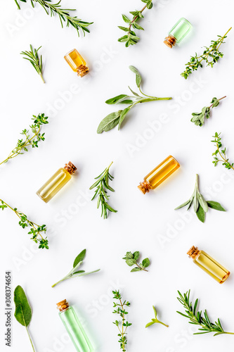 Fototapeta Essential oils and fresh herbs on white background top view pattern obraz