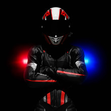 Beautiful Motorcyclist In A Leather Suit, Helmet With A Black Visor. Motorcyclist In The Dark. Behind Him, The Red And Blue Lights Of A Police Car