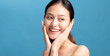 Portrait of confident beautiful asian woman with hand beside face and smiling isolated on blue color background with studio shot.Skincare for healthy face concept.