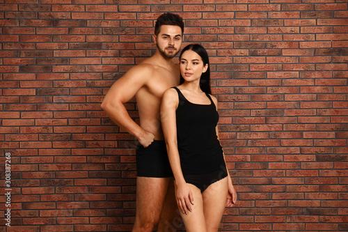 Fotografie, Obraz Young couple in black underwear near brick wall