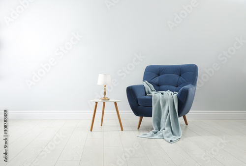 Stylish armchair with plaid, table and lamp near white wall Fototapeta