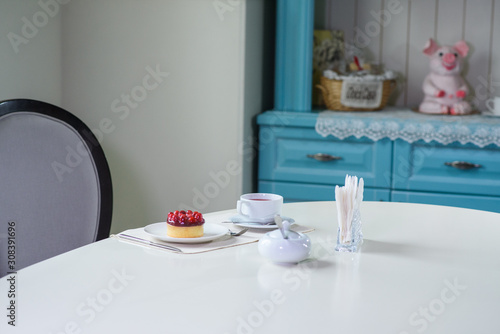 Fototapety, obrazy: Delicious berry tea and tarte with raspberries prepared on a table for a guest in a cozy cafe