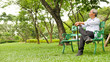 canvas print picture - Happy asian man sitting on a bench at the park.