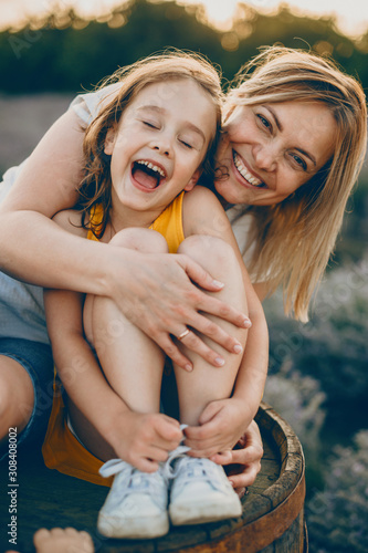 Fotografia Portrait of a lovely little girl laughing with closed eyes while is embraced by her mother with is laughing and looking at camera against sunset