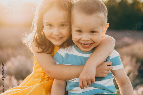 Close up of a cute little brother and sister embracing and looking at camera laughing while sitting in a field of flowers at sunset Tablou Canvas