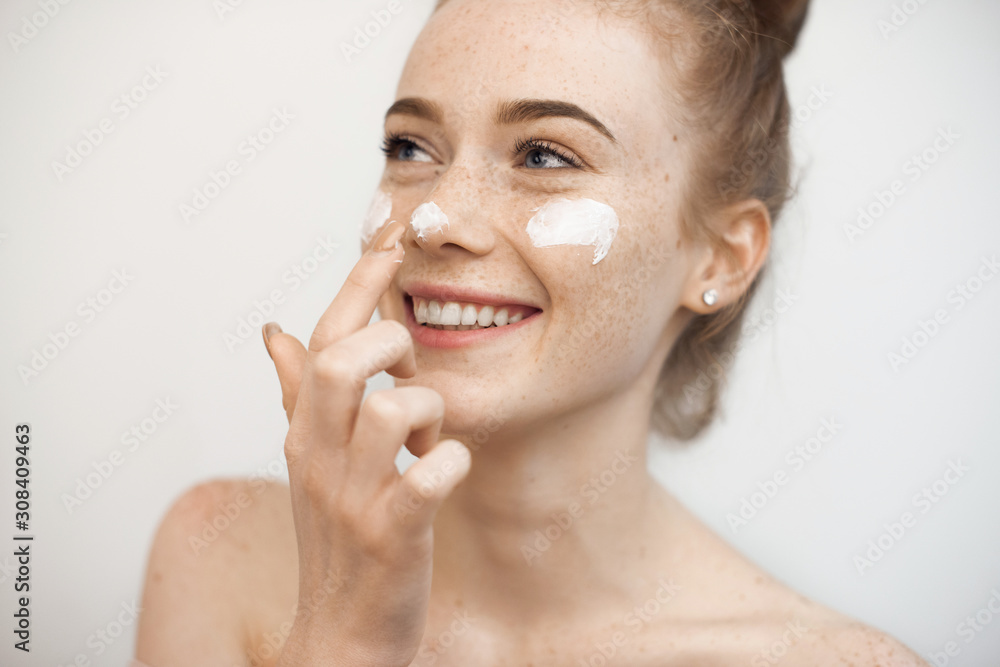 Fototapeta Portrait of a charming young female with red hair and freckles isolated on white applying a anti age cream on her face and nose smiling.