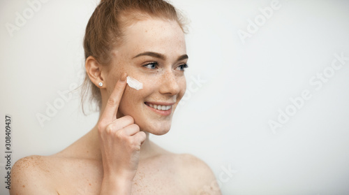 Fotografija Close up portrait of a beautiful woman with red hair and freckles looking away smiling while applying a white cream on her face isolated