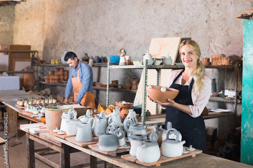 Portrait of glad woman pottery worker with ceramic crockery Canvas Print