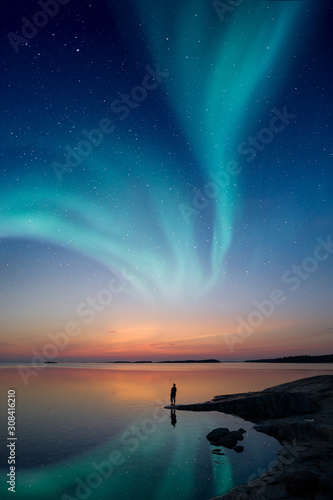 Fototapeta A man standing by a calm water and looking at the northern lights on the sky with reflections from the water obraz