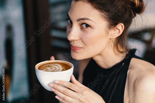 Fototapeta Refined Woman Enjoying Cappuccino or Latte on a vibrant, colorful background indoors. obraz
